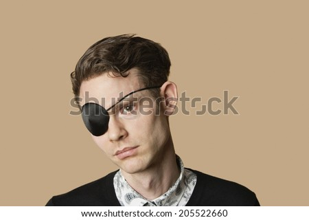 Sad mid adult man wearing eye patch over colored background - stock photo