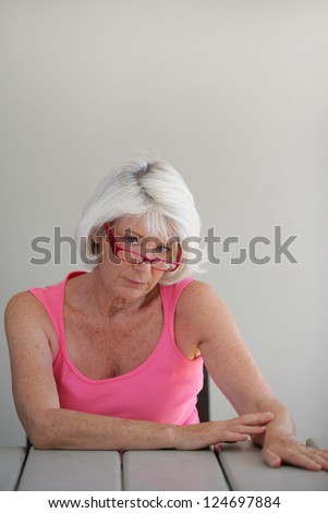 Sad middle-aged lady sat at a table - stock photo
