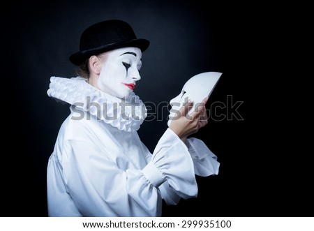 Sad mime Pierrot looking at the mask  - stock photo