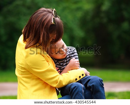 Sad mother and son in summer green park - stock photo