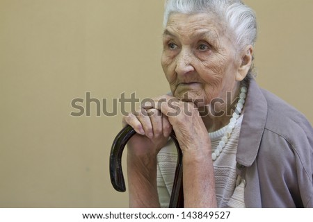 sad old lady's portrait with a walking stick  in front of a light brown wall