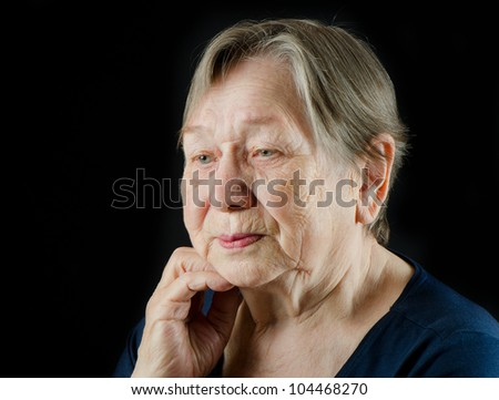 Sad old senior woman looking down and crying - stock photo