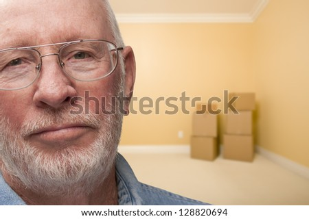 Sad Older Man In Empty Room with Boxes - Concept for Foreclosure, Divorce, Moving, etc. - stock photo