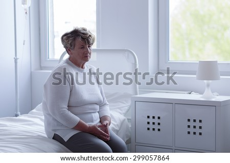 Sad older woman left alone in hospital - stock photo