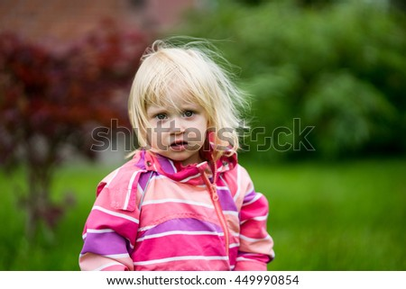 Sad or bewildered girl standing alone in the garden - stock photo