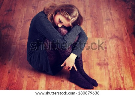 Sad or depressed woman sitting on the flor