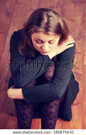 Sad or depressed woman sitting on the flor - stock photo