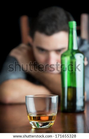 Sad out of focus man staring at a glass of liquor (focused on the glass)