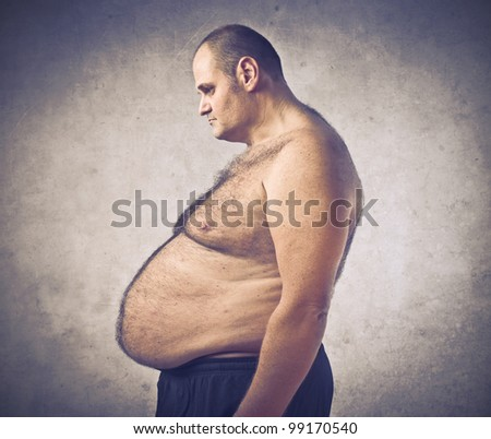 Sad overweight man looking at his belly - stock photo