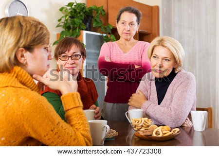 sad   pensioners drinking tea and sharing problems at table  indoor - stock photo