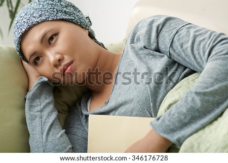 Sad pensive cancer survivor in headscarf lying on the sofa - stock photo
