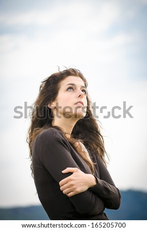 Sad pensive woman shivering, hugging herself and feeling low. Female emotional depression and sadness. Curly hair caucasian model. - stock photo