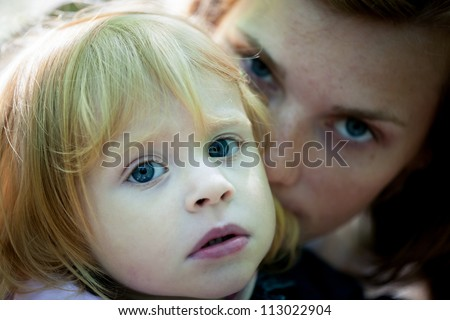 Sad portrait of mother and daughter - outdoor - stock photo