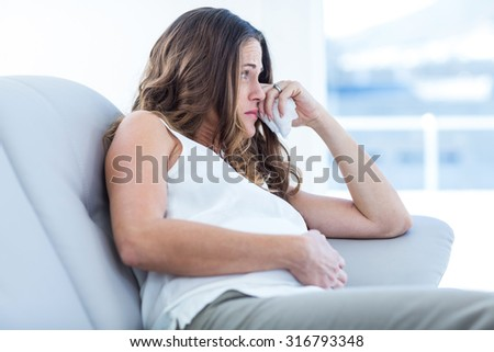 Sad pregnant woman sitting on sofa at home - stock photo