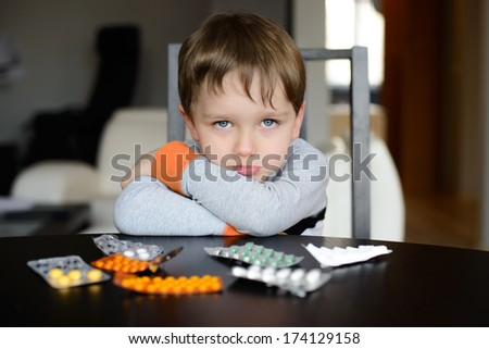sad preschooler sitting at the table with pills at home - stock photo