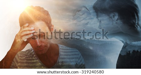 Sad pretty brunette leaning against wall against trees and mountain range against cloudy sky - stock photo