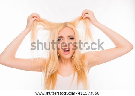 Sad pretty girl showing her damaged hair - stock photo