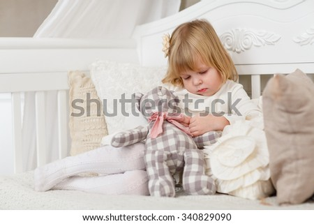 Sad pretty girl with toy bear sits on a sofa in the room. - stock photo