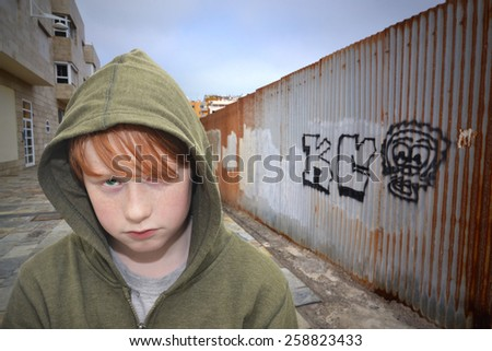 sad redhead boy standing on a lonely street