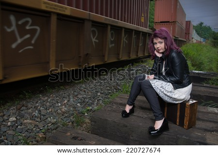 Sad runaway teen girl waits for train to escape her problem - stock photo