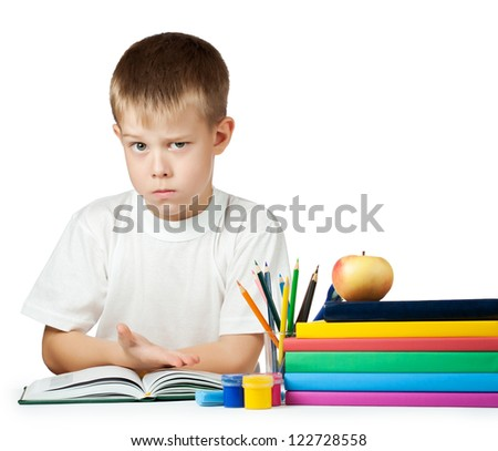 sad schoolboy is doing his homework. isolated