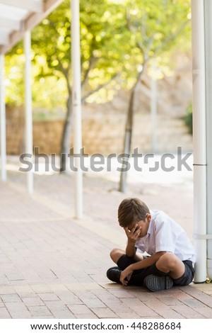 Sad schoolboy sitting alone in corridor at school - stock photo