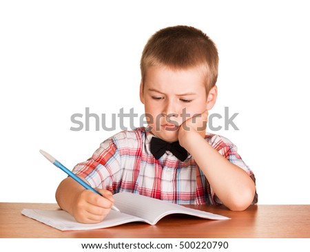 Sad schoolboy with a pen in his hand sitting at a desk on a notebook isolated on white background.