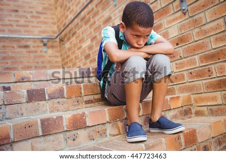 Sad schoolboy with his head on his knee in the stairs