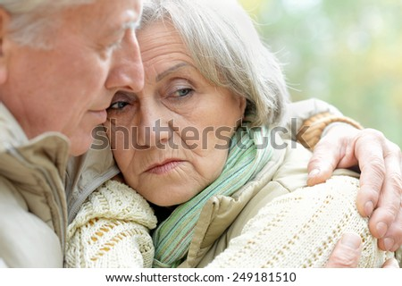Sad senior couple standing in autumn park - stock photo