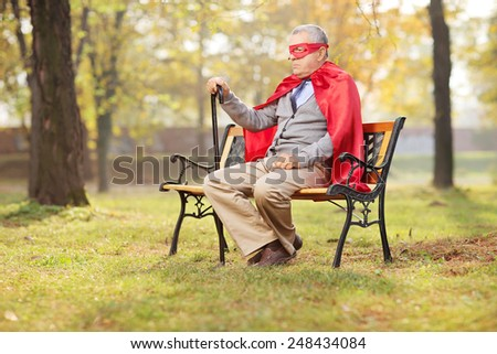 Sad senior in superhero outfit sitting in park on a wooden bench - stock photo