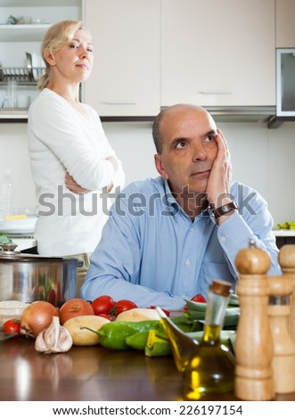 Sad senior man and  woman during quarrel  in kitchen at home - stock photo