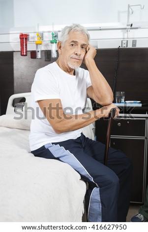 Sad Senior Man Holding Cane At Rehab Center - stock photo