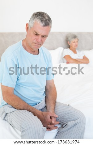 Sad senior man sitting on bed with wife in background at home