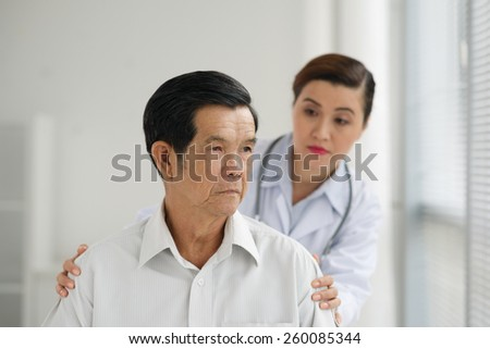 Sad senior patient with his caregiver in background