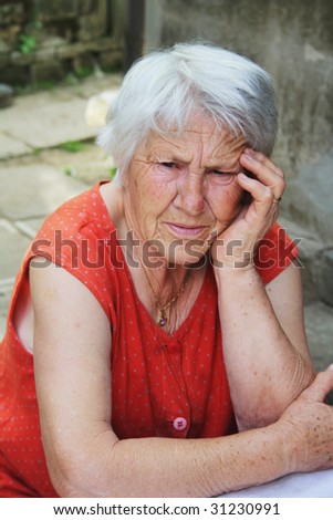 Sad senior woman holding her hand over head