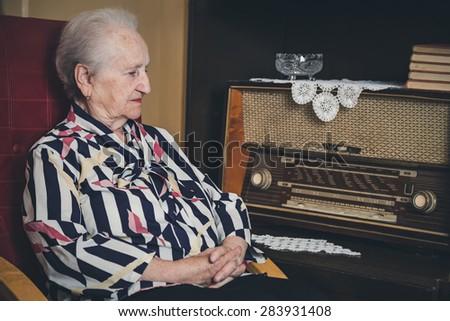 Sad senior woman sitting in a chair - stock photo
