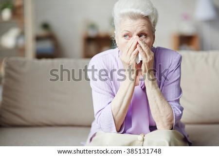 Sad senior woman sitting on sofa and crying - stock photo