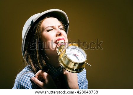 Sad shocked young woman in checkered shirt and pith helmet holding alarm clock over brown background - stock photo