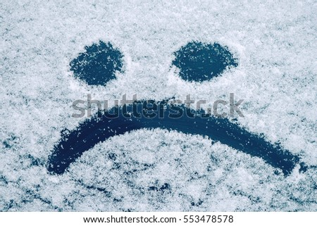 Sad smiley emoticon face drawn on snow covered glass, winter season sadness concept