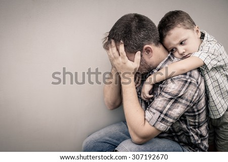sad son hugging his dad near wall at the day time - stock photo