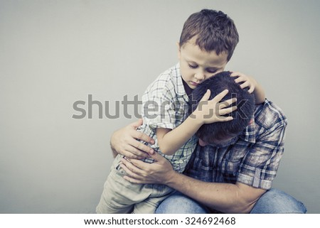 sad son hugging his dad near wall of house at the day time - stock photo