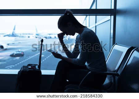 Sad/stressed/sick woman at the airport holding smart phone - stock photo