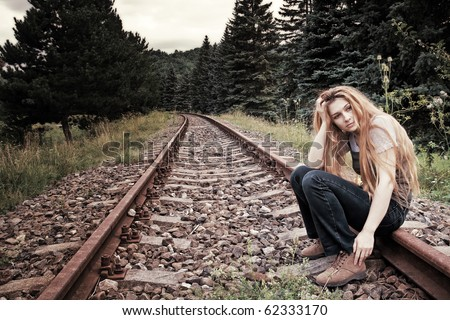 Sad suicidal lonely young woman on railway track - stock photo