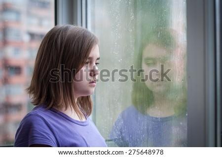 sad teen girl looking into rain window - stock photo