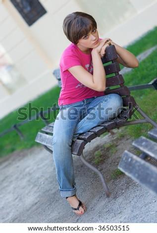 sad teen girl on the park bench - stock photo