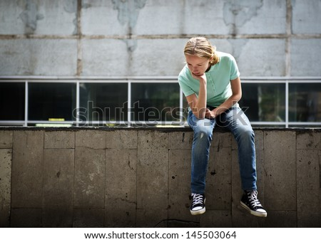 Sad teen girl sitting on a concrete parapet. Real people series - stock photo