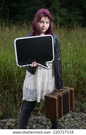 Sad teen runaway girl holds chalkboard for your text - stock photo