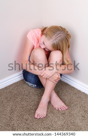 Sad teen sitting in corner with sad look on her face