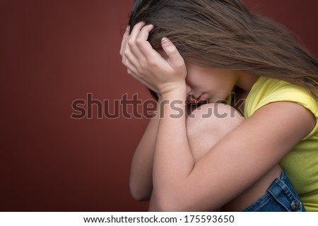 Sad teenage girl crying (with space for text) - stock photo