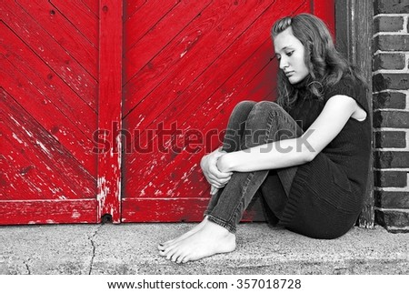 sad teenage girl huddled by bright red wooden door